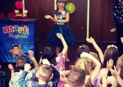 Marli leading the children in singing happy birthday at this party in Bexley